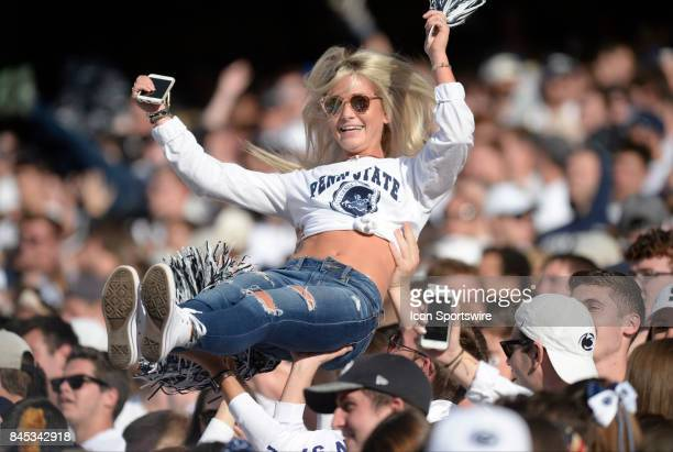 A female girl Penn State fan wearing a jersey is lifted in the air and waves a pom pom in the student section after a TD The Penn State Nittany Lions...