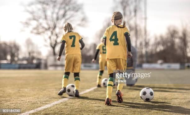 Female Girl Soccer Team running drills at football training