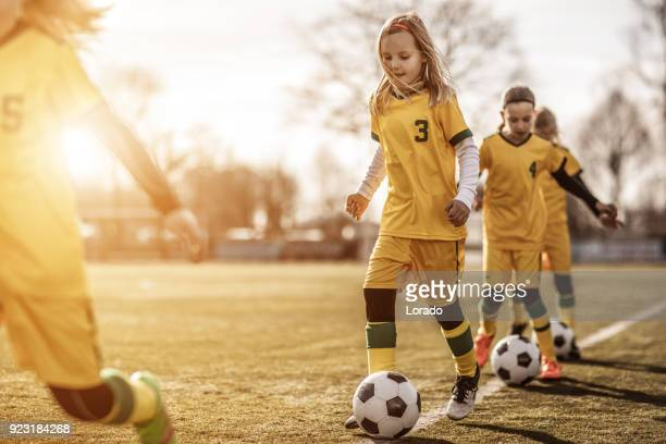 Female Girl Soccer Team running drills at football training