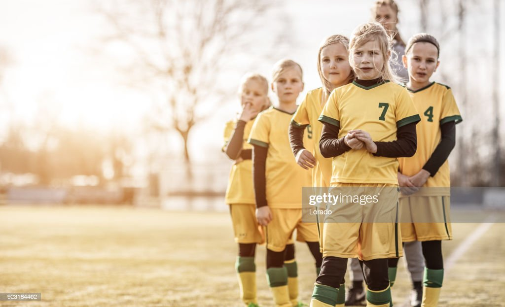 Female Girl Soccer Team running drills at football training with their coaches : Stock Photo