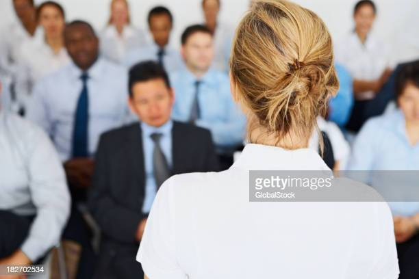 Female giving presentation to her business colleagues