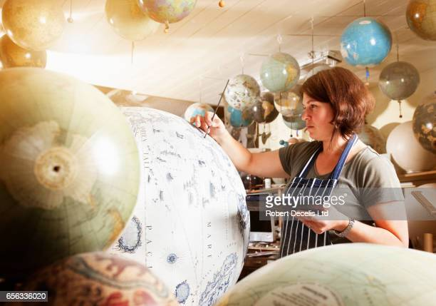 Female globe maker applying detail by hand to large globe