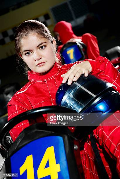 Female go-cart racer sitting in a sports car and thinking