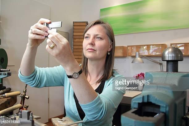 female goldsmith taking measurements in workshop - sigrid gombert stock-fotos und bilder