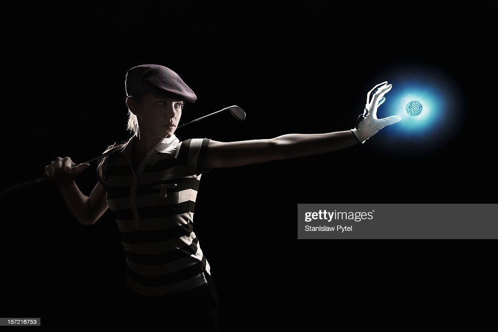 female golf player holding glowing ball : Stock Photo