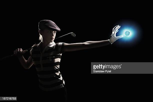 female golf player holding glowing ball