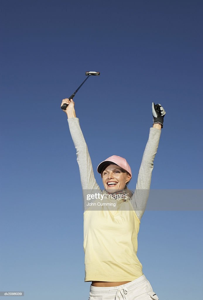 Female Golf Player With Her Arms Up : Stock Photo