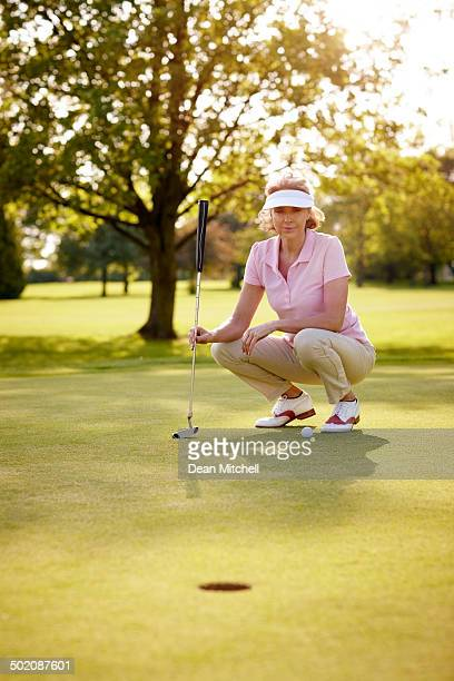 female golfer aiming for her putt shot - women's golf stock pictures, royalty-free photos & images