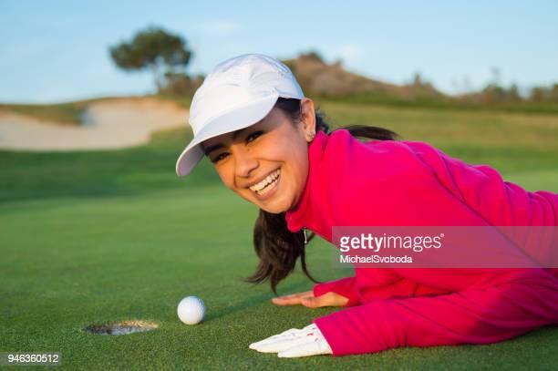 golfspielerin bläst ihr golfball ins loch - golf lustig stock-fotos und bilder