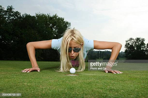 female golfer blowing on ball by hole - golf lustig stock-fotos und bilder