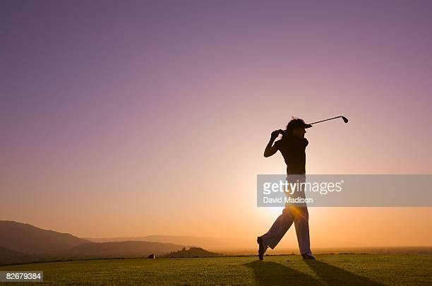 Female golfer follows through after driving ball.
