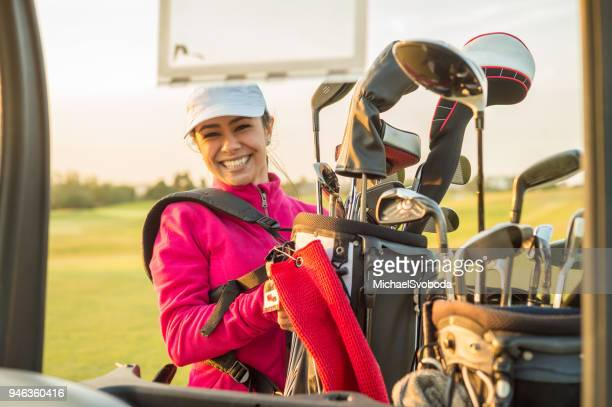 Female Golfer Grabbing clubs out of her golf bag at sunset.