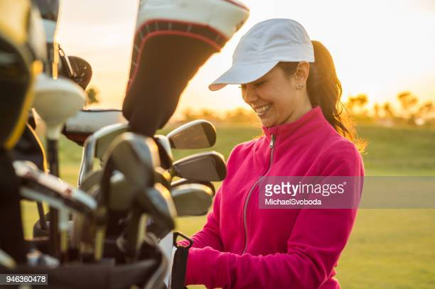 female golfer grabbing clubs out of her golf bag at sunset. - golf stock pictures, royalty-free photos & images