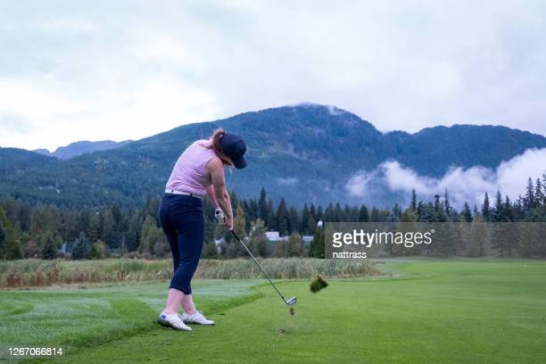 female golfer hitting the perfect golf shot towards the green - teeing off stock pictures, royalty-free photos & images