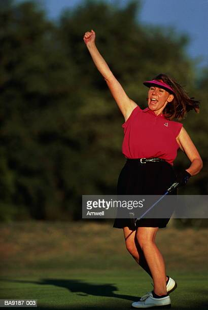 Female golfer holding putter,with arm raised in celebration