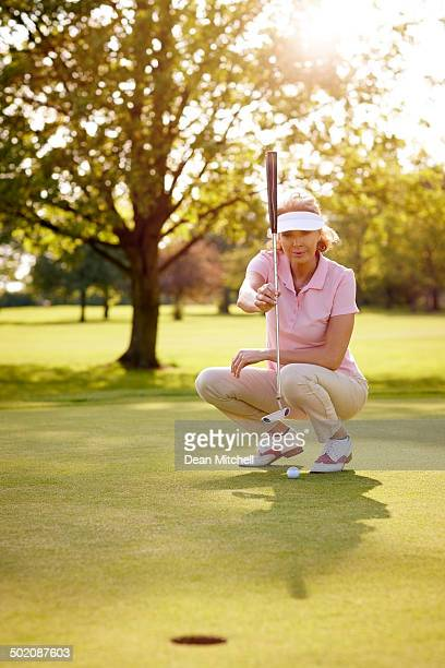 female golfer lining up for her shot - women's golf stock pictures, royalty-free photos & images