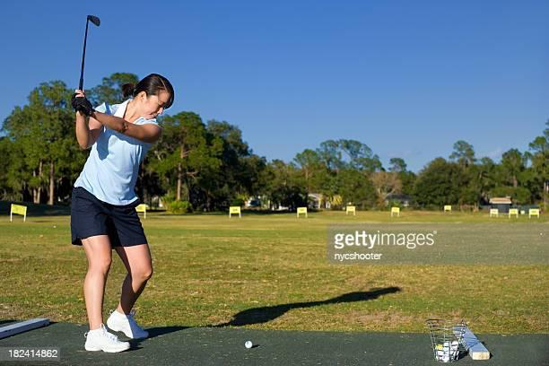 女性のゴルフ練習場での練習