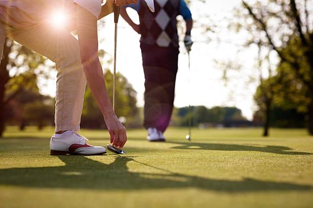 Golfeuse Récupérant Une Balle De Golf Du Trou - Photos et images libres de droits