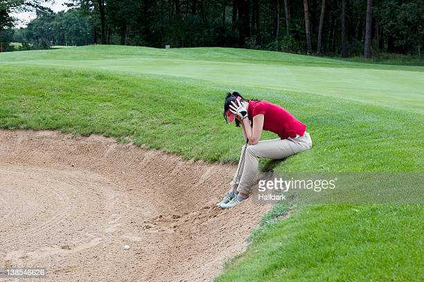 a female golfer sitting at the edge of sand trap, head in hands - バンカー ストックフォトと画像