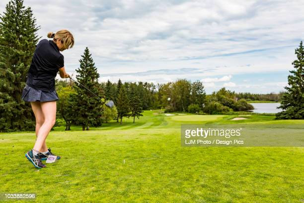 a female golfer skillfully driving a golf ball down the green grass of a golf course with the ball in mid-air - ティーショット ストックフォトと画像