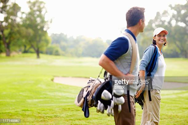 Female golfer smiling and looking at man