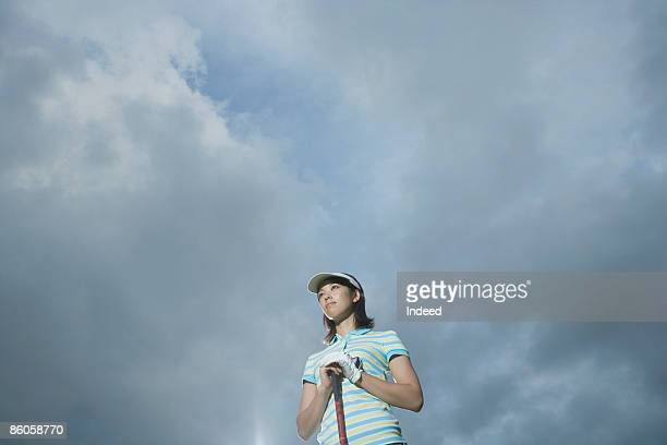 Female golfer standing, low angle view