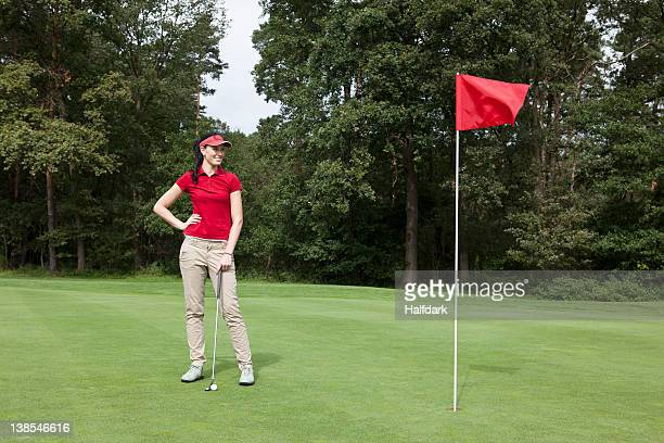 a female golfer standing on a putting green - red pants stock pictures, royalty-free photos & images