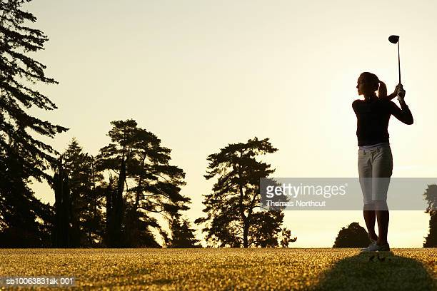 Female golfer swinging club on golf course at sunset