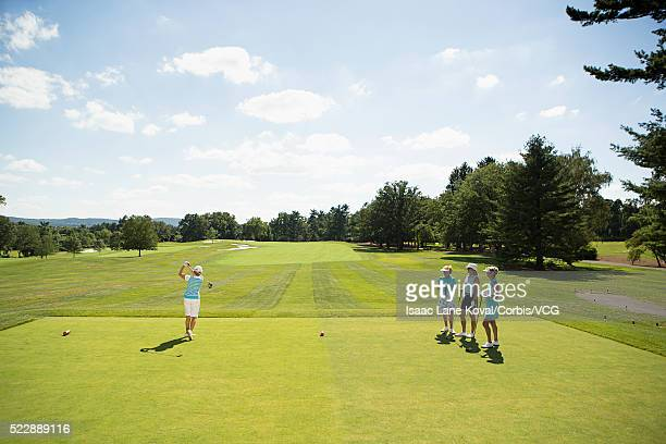 female golfer swinging while being observed by her friends - ティーグラウンド ストックフォトと画像