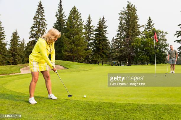 a female golfer swings and makes a putt while her teammate helps to mark the terrain to assist her at the hole on a golf course - putting stock pictures, royalty-free photos & images