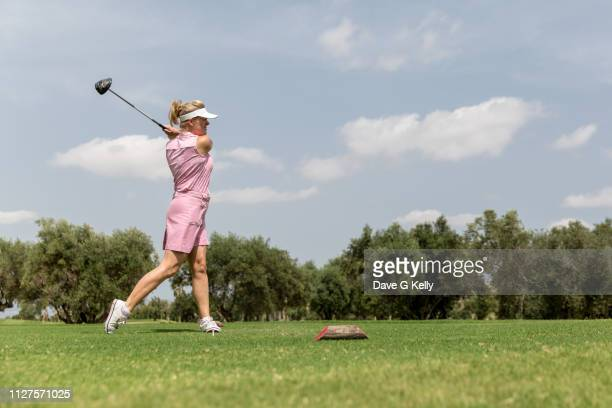 a female golfer teeing off - teeing off stock pictures, royalty-free photos & images
