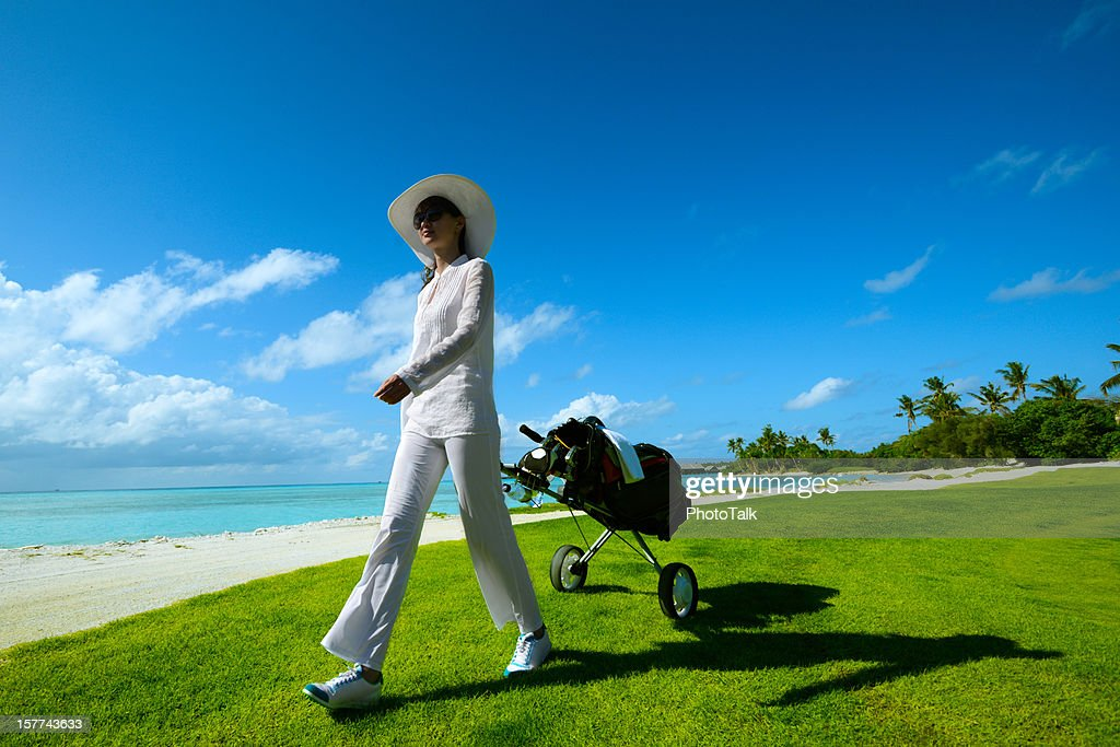 Female Golfer With Cart Walking On Beach Golf Course : Stock Photo