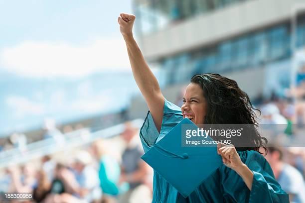 Female graduate raising fist