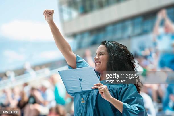 female graduate raising fist - graduation crowd stock pictures, royalty-free photos & images
