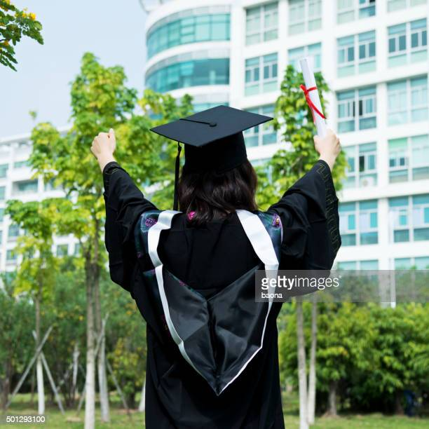 Female graduate student with hands raised