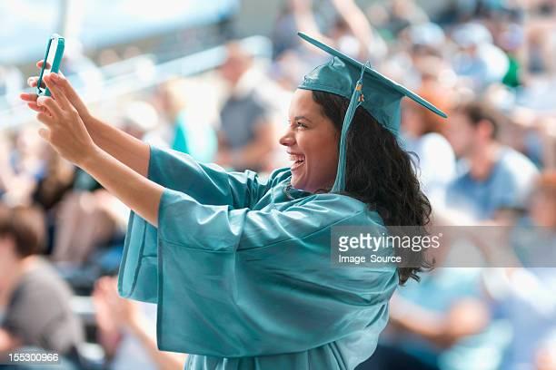 Female graduate taking photograph of herself