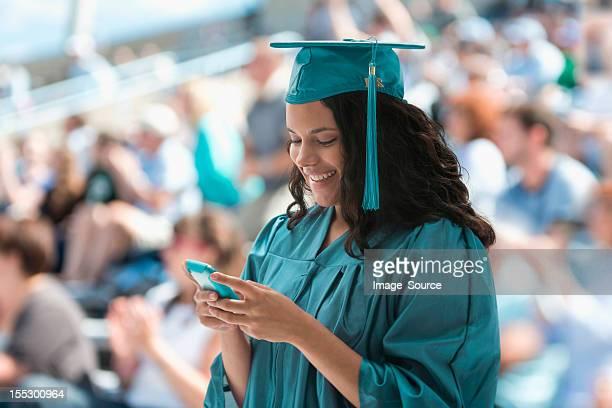 Female graduate using smartphone