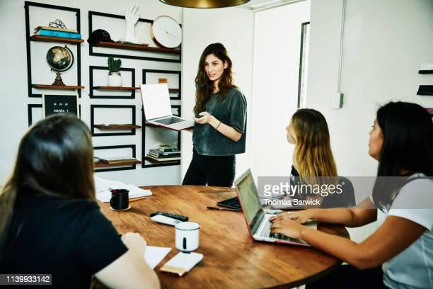 female graphic designer presenting project ideas to colleagues during meeting - métier du design photos et images de collection