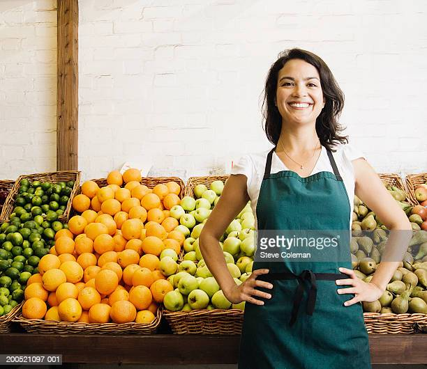 Female greengrocer at market stall, smiling, portrait