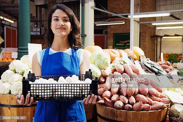 Female greengrocer holding box of mushrooms at market stall, portrait