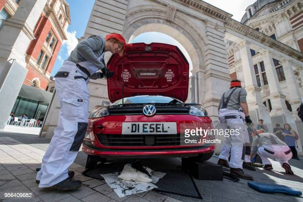 Female Greenpeace activists dismantle a Volkswagen diesel car during a protest in the street outside the launch of the new exhibition 'The Future...
