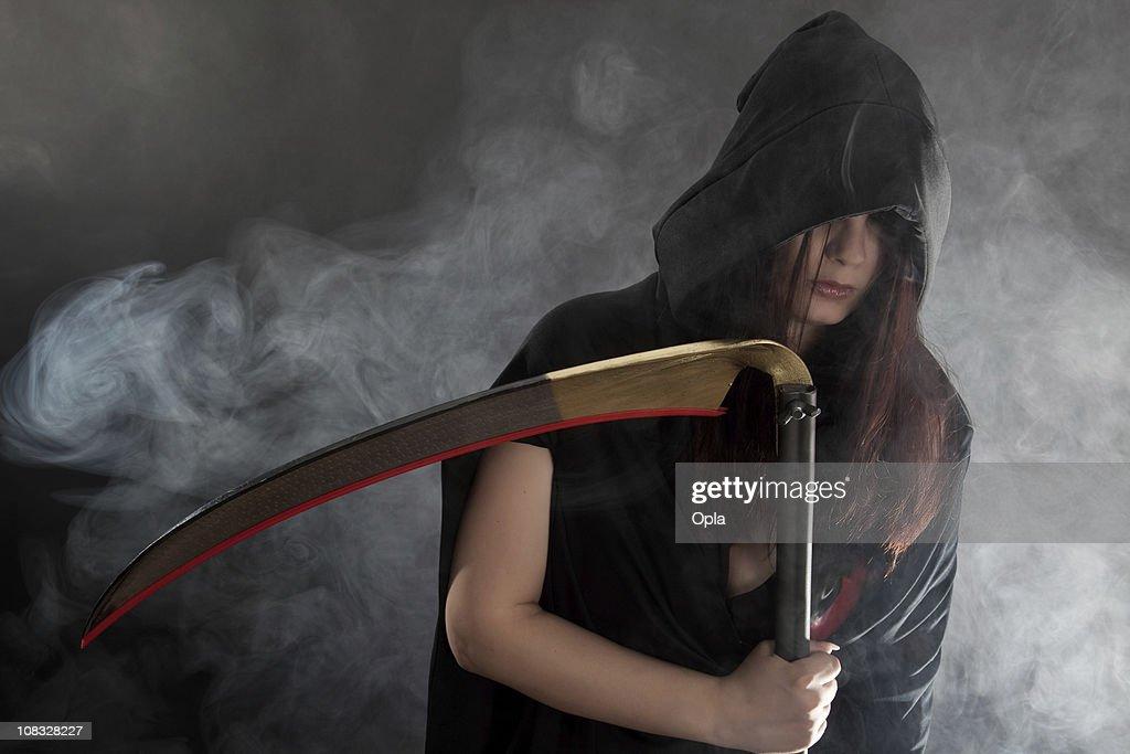 Female Grim Reaper holding a scythe : Stock Photo