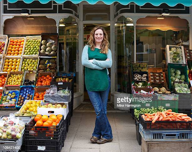 Female Grocer at Shop Entrance