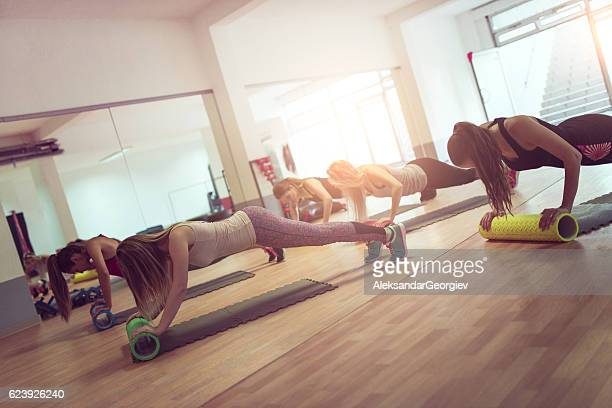 female group exercise in gym with cylindrical rollers on floor - pilates foto e immagini stock