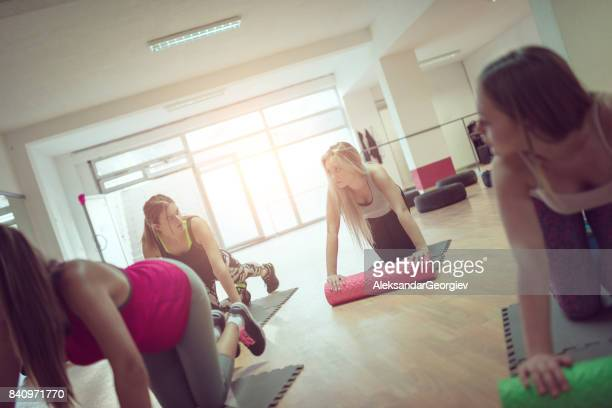Female Group Exercise in Gym with Cylindrical Rollers on Floor