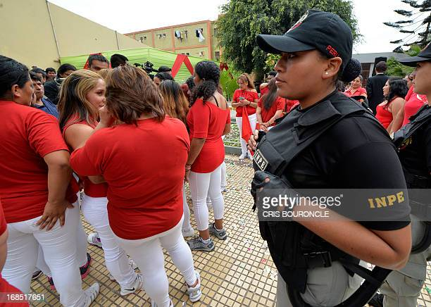 A female guard of the Peruvian National Penitentiary Institute stands guard as the inmates celebrate Mothers Day two days in advance of the...