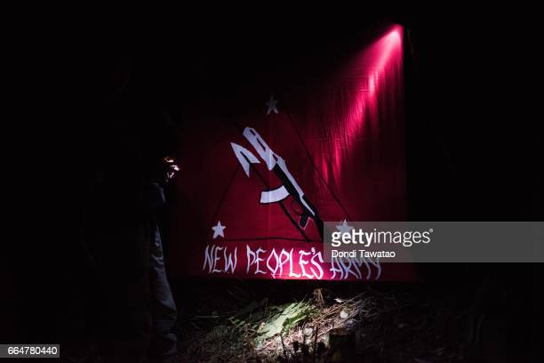 A female guerillas of the New People's Army apply paint on a NPA flag on April 1 2017 in the remote hinterlands of Mountain Province Philippines The...