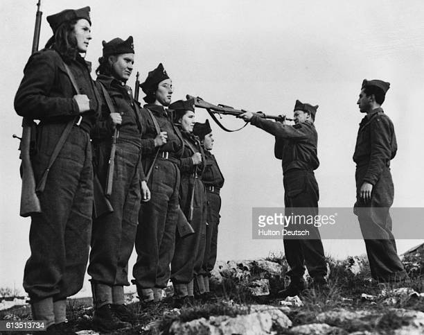 Female guerrilla fighters from the Yugoslav Partisans, or People's Liberation Army, stand at attention as a commander inspects their rifles. Fresh...