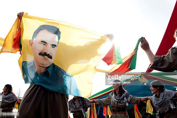 Female guerrillas dance a traditional Kurdish dance while holding a flag depicting Apo Ocalan the spiritual leader of the PKK and PJAK The PJAK is a...