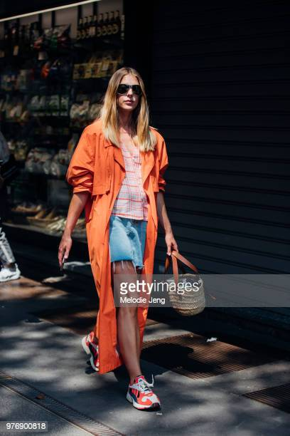 A female guest in an orange jacket and sneakers during Milan Men's Fashion Week Spring/Summer 2019 on June 16 2018 in Milan Italy